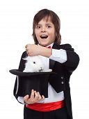 Young magician boy taking a cute white rabbit out of the hat - excited by his success