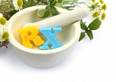 Mortar with fresh herbs and colorful letters RX isolated on white