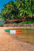 Sandy Beach In The Tropics And Canoes By The River