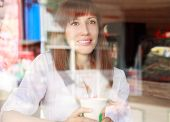 Young Smiling Woman Behind Glass Of Cafe