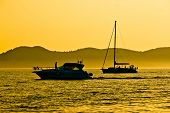 Yacht And Sailboat Silhouette At Golden Sunset