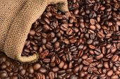 Closeup of a burlap sack of fresh roasted coffee beans spilling onto a table. The beans fill the frame. Horizontal format.