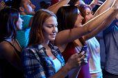 party, holidays, celebration, nightlife and people concept - smiling young woman with smartphone texting message at concert in club
