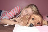 Girl and her dog sleeping together on a bedroom