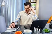 Young businessman sitting at desk, working with laptop and calculator.