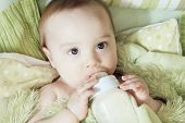 foto of teething baby  - Funny little baby with beautiful standing in a round white crib - JPG