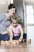 Relaxed mother and daughter playing with building blocks on wood