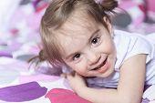 foto of shy girl  - Little girl lying on bed in room - JPG