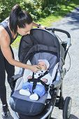 stock photo of buggy  - A Young mother jogging with a baby buggy - JPG