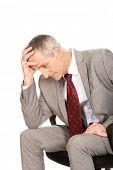 Stressed mature businessman sitting on armchair.