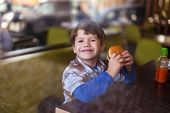 stock photo of hamburger  - Little boy smile with hamburger in fast food restaurant behind glass - JPG