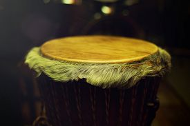 pic of congas  - Original african djembe drum with leather lamina with beautiful hair in beautiful tyellow light with dark background - JPG