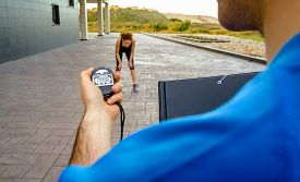 stock photo of chronometer  - Closeup of man trainer hand using a chronometer to timing at tired athletic young woman in a hard training outdoors - JPG