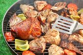 stock photo of grill  - Spatula BBQ Assorted Meat And Vegetables On The Hot Flaming Grill - JPG