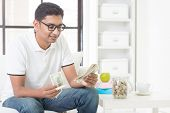 image of indian currency  - Indian guy counting money and smile at home - JPG