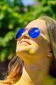 image of holi  - girl with multicolored face and sunglasses at Holi Festival - JPG