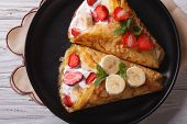 stock photo of crepes  - homemade crepes with fresh strawberries bananas and cream close - JPG