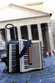 stock photo of accordion  - Accordion and harmonica in the background of Pantheon in Rome - JPG