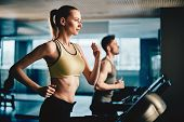stock photo of treadmill  - Pretty woman running on treadmill with fit young man on background - JPG