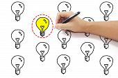 picture of dash  - hand with pen drawing selected red dash circle around yellow light bulb idea among many on pure white background - JPG