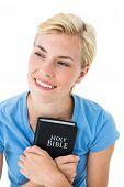 foto of pentecostal  - Pretty smiling blonde woman holding bible on white background - JPG