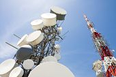 stock photo of telecommunications equipment  - mobile phone and telecommunication towers against blue sky - JPG