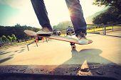 picture of skateboard  - skateboarder riding on skateboard at skatepark ramp - JPG