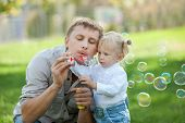 stock photo of father daughter  - A dad and his daughter are making bubbles in the park - JPG