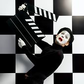 stock photo of comedy  - Movie actor and a mime posing with clapper board with different emotions - JPG