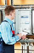 foto of fuse-box  - electrician builder engineer inspector checking data of equipment in fuse box - JPG