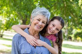 stock photo of grandmother  - granddaughter and grandmother smiling in a park on a sunny day - JPG