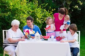 stock photo of grandparent child  - Big family with children have lunch outdoors - JPG