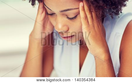 people, emotions, stress and health care concept - unhappy african american young woman touching her