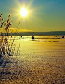 Winter fishermens on ice under sun