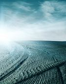 Blue light over abstract soil with furrows