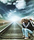 Alone woman sitting on railroad under blue sky