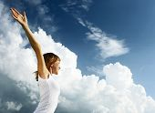 Young woman in white shirt over blue sky with fluffy clouds poster