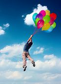Young man flying in blue sky holding group of colored balloons. Balloons is illustration