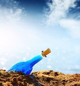 Blue empty bottle in coast sand and blue sky with clouds