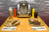 1950's style diner table with juke box, malt, cola, hot dog and hamburger.
