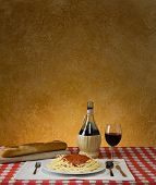 Spaghetti dinner with a baguette and Chianti on a red checkered table cloth with ample background fo