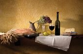 Bread, wheat, wine, cheese, grapes against a rustic plaster wall