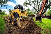 Yellow Mini Bulldozer Working With Earth, Moving Soil And Doing Landscaping Works poster