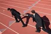 image of relay  - Businessmen passing the baton in a track relay - JPG