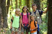 Four children in woods with camping gear