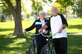 stock photo of senior adult  - Senior couple at park with bikes - JPG