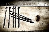Screws and ruler on a grunge wood background/ Ideal for construction concepts, business card, etc...