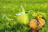Gießkanne im Gras mit alten Strohhut