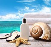 Sunblock lotion and white towels with ocean scene