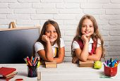 Back To School And Home Schooling. Happy School Kids At Lesson In September 1. Little Girls Eat Appl poster